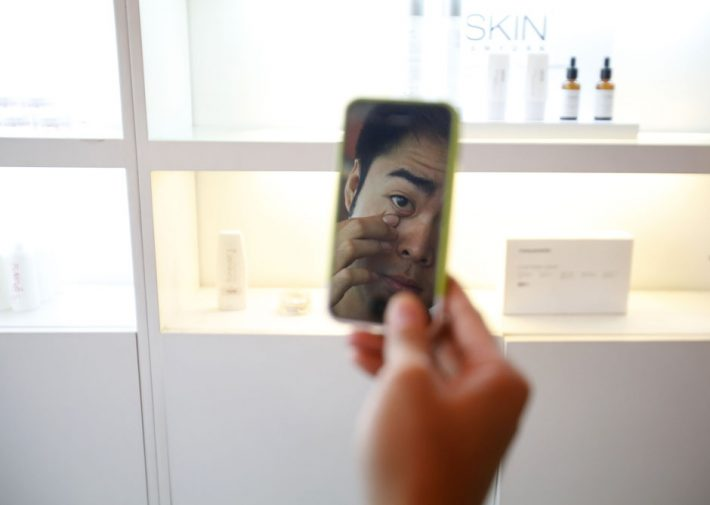 Ryan Estipona uses his mobile phone as a mirror, as he waits for a facial treatment, which costs $21 (880.00 pesos), at a skin care clinic in a mall in Quezon City Metro Manila May 24, 2013. Men's beauty treatments are popular in the Philippines, part of a thriving market for male cosmetics in the Asia Pacific region. Some Filipino men go to great lengths to preserve their faces, from those who visit clinics to receive skin treatments, to fishermen who wear fabric masks while working to protect their skin from the sun. Picture taken May 24, 2013. REUTERS/Cheryl Ravelo (PHILIPPINES - Tags: SOCIETY HEALTH) ATTENTION EDITORS: PICTURE 03 OF 31 FOR PACKAGE  'MALE BEAUTY, MANILA STYLE' SEARCH 'MALE BEAUTY' FOR ALL IMAGES
